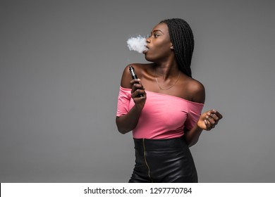 African woman smoking or vaping e-cig or electronic cigarette holding a mod with a lot of clouds on black background