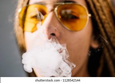 African woman smoking white smoke hookah.