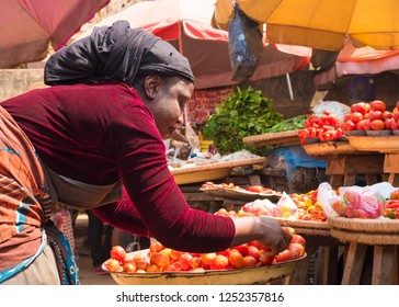 african woman sorting tomatoes she's selling in a local african market
