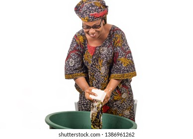 African woman standing above the laundry bowl washes clothes with a big piece of white soap isolated on white background.