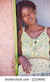 african woman standing in front of the door , village in Botswana