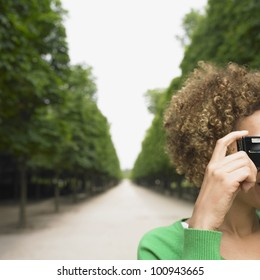 African woman taking photograph in park