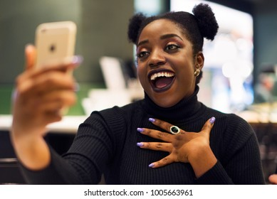 An African woman taking a selfie in a cafe, she has a very happy expression.