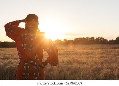 African woman in traditional clothes looking across a field of barley or wheat crops at sunset or sunrise