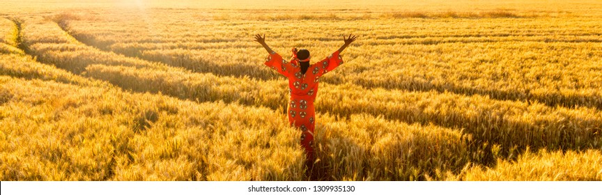 African woman in traditional clothes standing, arms raised, in field of barley or wheat crops at sunset or sunrise panoramic web banner