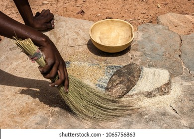 An african woman using her fiber broom after having ground cereals (millet/sorghum) in Burkina Faso. Tools : grindstones, fiber broom, calebash.