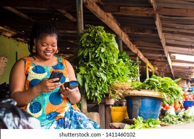 african woman using her phone and also holding a pos system in a local market