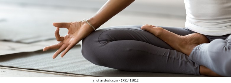 African woman wearing active wear do yoga practice meditating indoors, close up cropped photo lotus position. No stress, mindfulness, inner balance concept. Horizontal banner for website header design - Shutterstock ID 1751415812