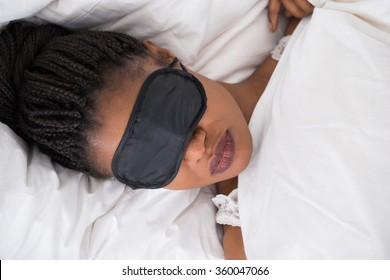 African Woman Wearing Eyemask While Sleeping On Bed