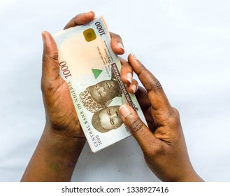 African woman's hand holding one thousand Naira Nigerian isolated on white background for payment concept with copy space for advert text for business concept