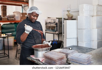 African worker standing at a table in an artisanal chocolate making factory mixing melted chocolate in bain marie with a spoon
