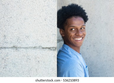 African young adult man behind wall with copy space