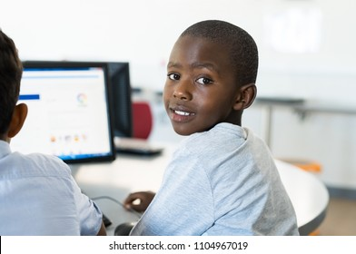 African young boy using computer in class. Portrait of happy schoolboy sitting at desk with laptop. Smiling black child looking at camera while classmate working on computer desktop.