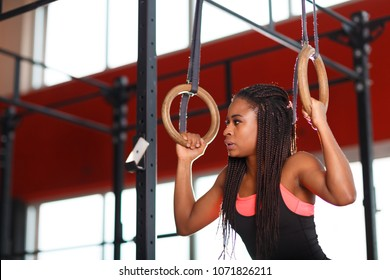 The African young fitness woman working out on flying rings in the athletic gym.  fitness concept.