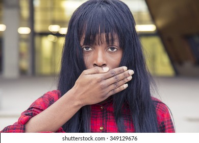African young girl covering her mouth