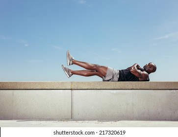 African young man doing stretching exercising while lying on a wall by walkway outdoors. Muscular young fitness model exercising against sky.