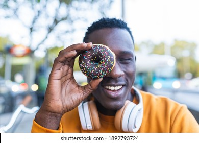 African Young Man Eating Donuts Outdoors. Black Man Eating Sweet Food While Smiling. Food Concept.