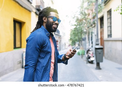African Young Man Using Mobile In The Street.