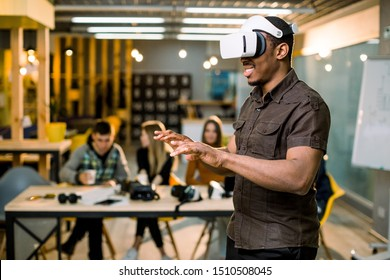 African young man wearing virtual reality glasses in modern interior design coworking studio. Smartphone using with VR goggles headset. Team of young people working at the table on the background