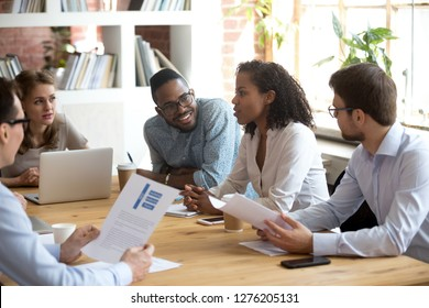 African young project manager speaking at diverse meeting sharing creative ideas telling opinion at group briefing, black female employee talking reporting about corporate work result, team listening