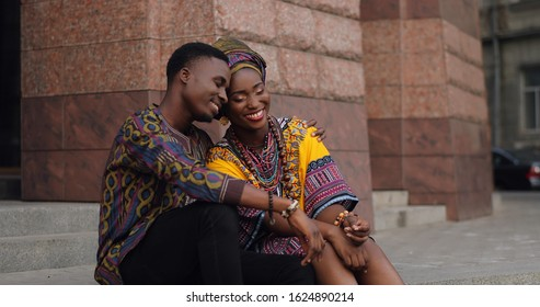 African young romantic and happy couple in love in the traditional outfits sitting on the steps in the town street and talking cheerfully.
