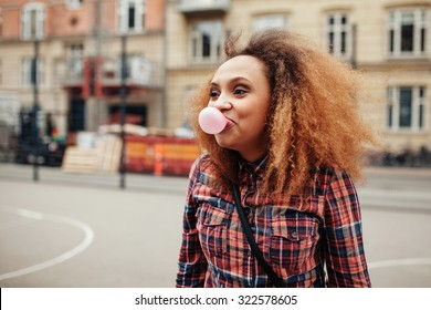 African young woman blowing a bubble with her chewing gum. Casual young woman on city street having fun.