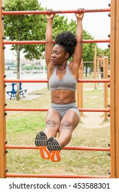 African young woman doing abdominal exercises in urban structures for sports in a city park