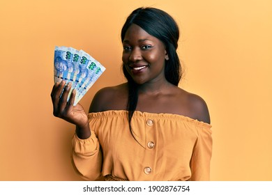 African young woman holding south african 100 rand banknotes looking positive and happy standing and smiling with a confident smile showing teeth