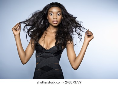African young woman with long hair wearing small bandage black dress on blue background.