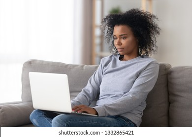 African young woman sitting in living room on couch typing message browsing web buying ordering goods via internet working on computer communicating with client online using electronic wireless device