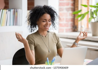 African young woman sitting at table opposite laptop in workplace meditating doing yoga exercise smiling feels good. Take a break, inner balance and harmony, stress relief no negative emotions concept