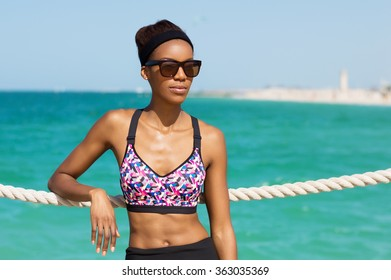 African young woman in sunglasses at the beach in Dubai, UAE