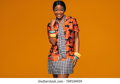 African young woman with vivid make up in studio. Portrait of fashion model standing against orange background.