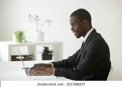 African-american attractive businessman in suit working on laptop in office, happy black ceo looking at computer screen typing mailing partners, browsing web, using software applications for business