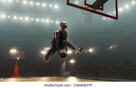 African-american basketball player scores a goal during a game on a professional basketball arena