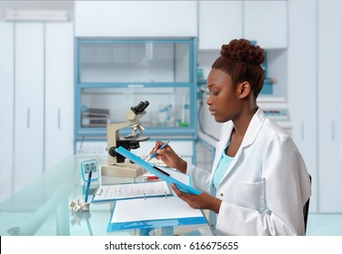 African-american biologist checks records in scientific lab or research facility. Focus on the face and eyelashes.