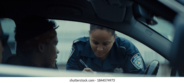 African-American black driver is being pulled off by mixed-race female police officer. Documents check, speeding ticket
