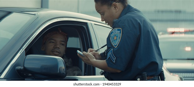 African-American black driver is being pulled off by mixed-race female police officer. Documents check, speeding ticket - Shutterstock ID 1940453329
