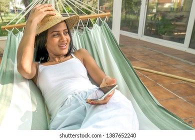 African-American black woman in a hammock with mobile phone and hat on vacation. concept of relaxation, rest, communication and technology on vacation