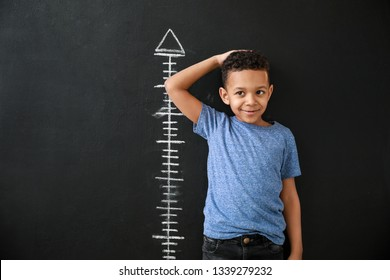 African-American boy measuring height near dark wall