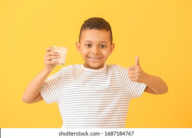 African-American boy with milk showing thumb-up on color background