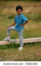 African-American boy standing and sitting in nature with grass field, flowers, wooden fence wearing blue print shirt and blue jeans