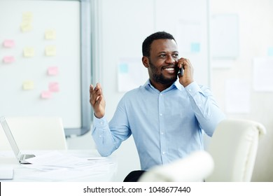 African-american business agent in formalwear speaking to client by smartphone while working in office