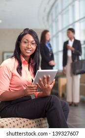 african-american business woman sitting in lobby with computer tablet, looking at camera, smiling, two business women in background