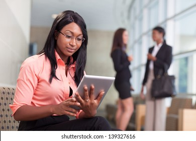 african-american business woman sitting in lobby, looking at tablet, two business women talking in background