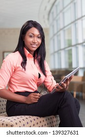 african-american business woman sitting in lobby with computer tablet, looking at camera, smiling