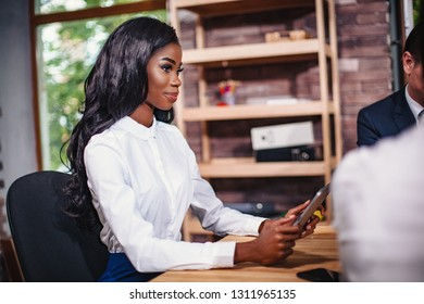 African-american business woman sitting at the table in the negotiations. She smiles and listens attentively to her business partners. Close-up shot