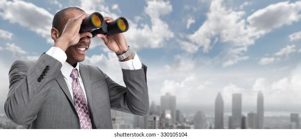 African-American businessman with binoculars over urban background.
