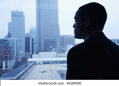 African-American businessman looking out of a window at the city. Horizontal shot.
