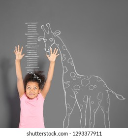 African-American child measuring height near chalk giraffe drawing on grey wall